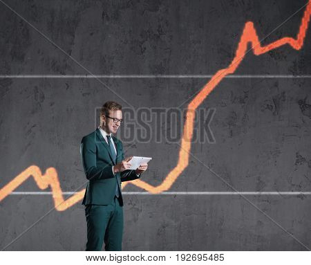 Businessman with computer tablet standing on a diagram background. Business, office, success, concept.