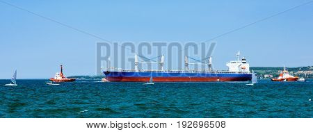 Cargo ship leaving the port with the help of tugboats