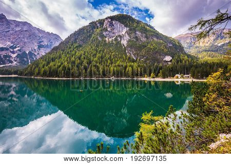 Magnificent lake Lago di Braies. The turquoise smooth surface of water reflects the wood and mountains around. Walk to South Tyrol, Italy. The concept of walking and eco-tourism