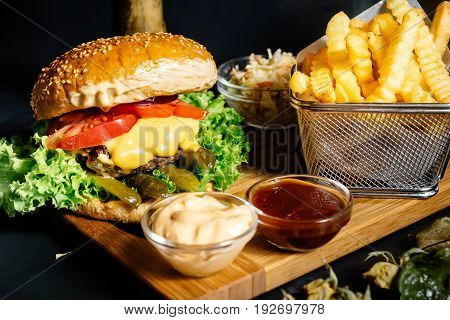 Tasty Grilled Beef Burger With Fresh Vegetables And French Fries Served Hot At Local Bistro