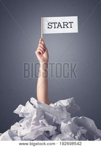 Female hand emerging from crumpled paper pile holding a white flag with start written on it