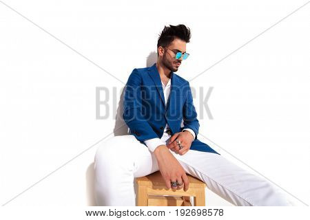 seated elegant man wearing rings on fingers and sunglasses looks down to side on white background