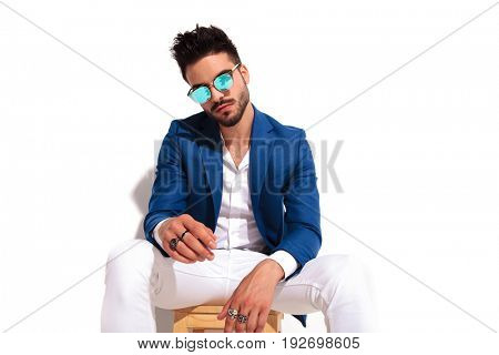 seated elegant young man resting elbows on knees and looks at the camera on white background