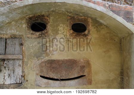 This wall in an old town in Tuscany, Italy, illustrates the phenomenong of Pareidolia, or seeing faces in things.