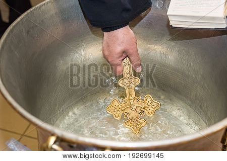 The priest blesses Christening Baptismal Font filled with Holy Water at the church during the ceremony at Sofia