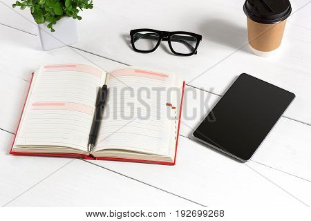 Stylish minimalistic workplace with tablet and notebook and glasses in flat lay style. White background. Top view. Copy space