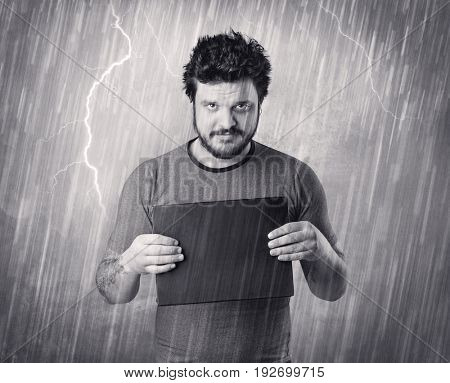 Caught gangster with rainy, grey background and black table on his hand.