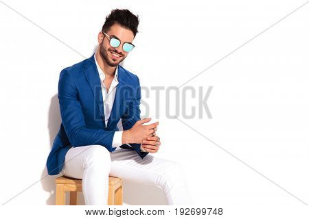 happy young elegant man wearing sunglasses and laughs while sitting on chair on white background