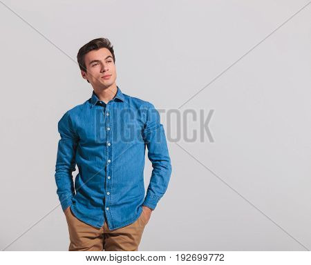 casual young man with hands in pockets looks away to side, thinking on grey background