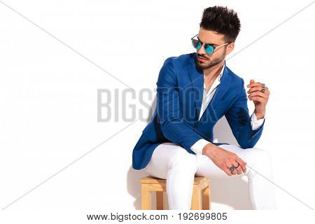 young fashion model wearing sunglasses and rings on his fingers is sitting on chair and looks to side on white background