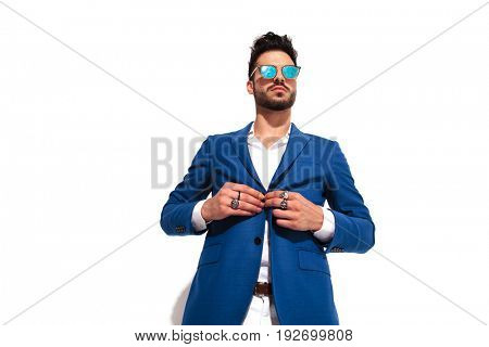 fashion man wearing rings and sunglasses unbuttoning his coat on white studio background