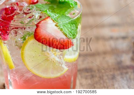 Strawberry lemon lime mojito in clear glass on rustic wood table. Homemade beverage strawberry soda ingredients with strawberry lemon or lime and mint leaf. Homemade infused water close up concept. Strawberry lemon soda in macro concept.