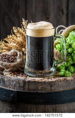 Pint Of Dark Beer With Ingredients On Old Barrel
