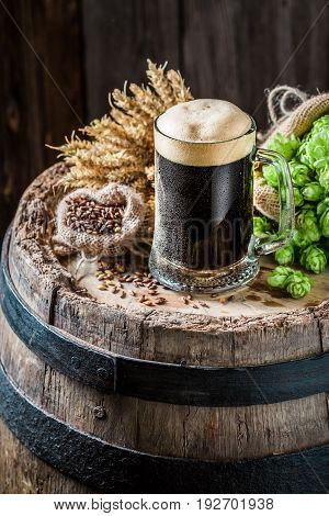 Cold Dark Beer On Oak Barrel With Hops And Wheat