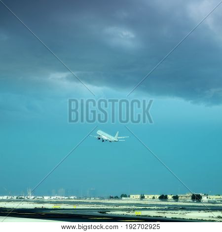 commercial airplane taking off from commercial airport over cloudy sky