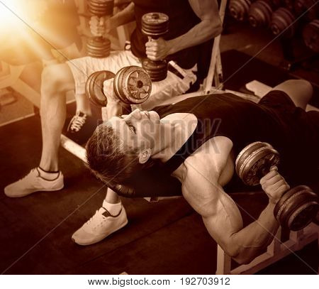 Men with dumbbells at gym. Group of friends training muscles at sport room. Color sepia tone on shiny sunlight background.