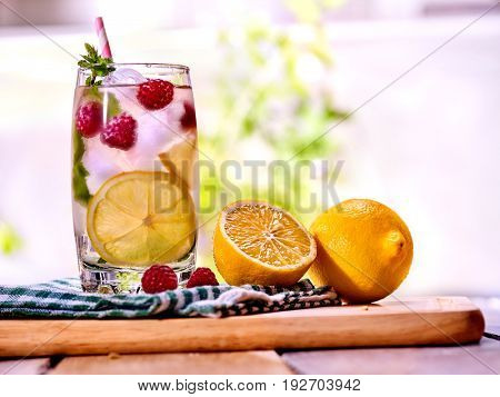 Cold water with lemon and mint leaf. Fresh raspberries lemonade with lemon slice and ice cubes. Non alcoholic beverage in cocktail glass on wooden board. Table setting rural style outdoor.