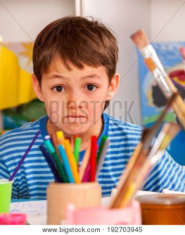 Small student boy painting in art school class. Child bad luck drawing by paints on table. Unhappy boy in children's club. Craft drawing education develops creative abilities of children. Drawing