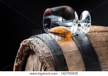 Glass Of Good Cognac On Oak Barrel