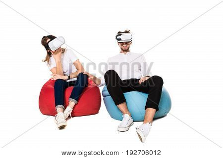 Excited young couple experiencing virtual reality seated on beanbags isolated on white background. A young couple dressed in jeans, white t-shirts and sneakers, VR