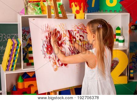 Child painting finger on easel. Girl learn paint in class school. Kindergarten interior on background. Picture with prints of children's hands. Free children's creativity.