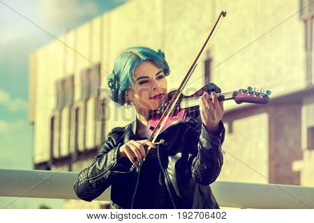 Music on violin by woman perform in park outdoor. Girl performing jazz on city street . Color tone on shiny sunlight background. Spring outside with blue hairstyle background.