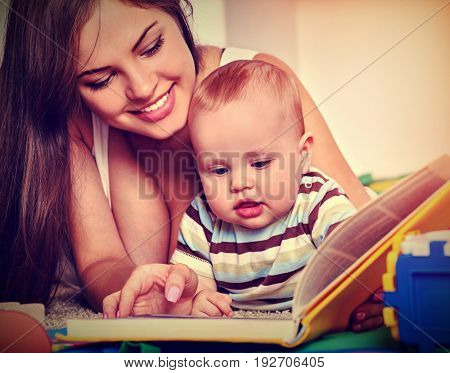 Family book read with mother and baby sitting floor. Early reading develops children. Sepia color tone image.