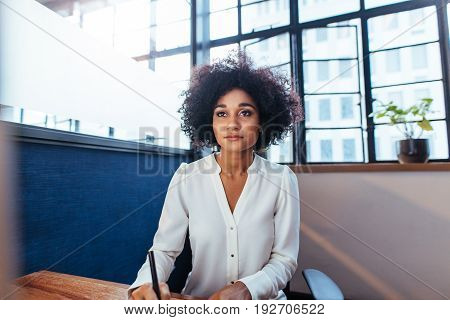 Indoor shot of young businesswoman sitting at her desk and working in office. African female executive working on computer.