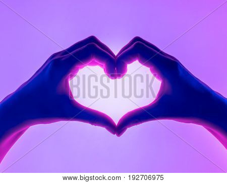 Hands in the form of heart violet background. heart symbol with hand. valentines day card. Woman's hands silhouette in form of heart. hand Gestures