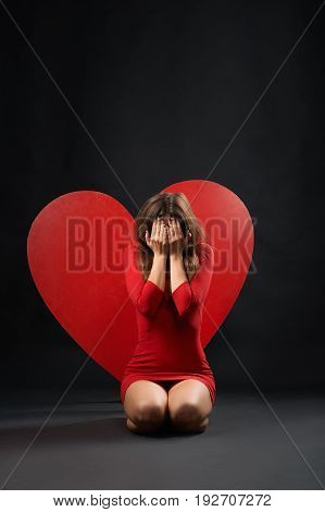 Vertical shot of a heartbroken woman crying sitting on the floor near big red heart symbol symbolic sign breakup relationships sadness depression depressed unloved pity unhappy emotions concept.