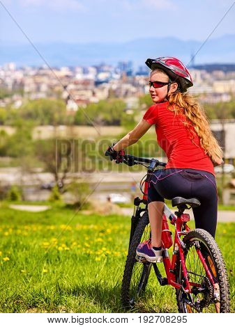 Escape urban . Bicycle girl has rest from city bustle. Woman wearing sport helmet returns home after hike in urbanization . Respect for environment. Back view. Return to civilization.