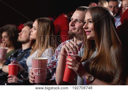 Attractive young woman smiling cuddling with her boyfriend while watching a movie together at the cinema dating love romance relationships people lifestyle entertainment leisure weekend concept.