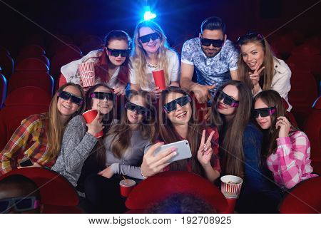 Happy young girl taking a selfie with a group of her friends at the cinema people wearing 3D glasses happiness positivity entertaining activity leisure togetherness celebration unity diversity.