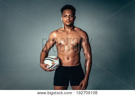 Studio shot of fit young man holding american football and looking at camera on grey background. African male model posing with a rugby ball.