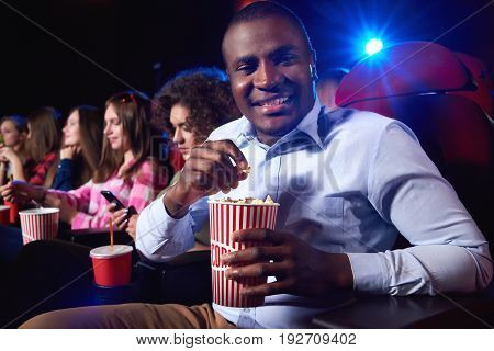 Cheerful young African man smiling to the camera holding his popcorn bucket enjoying a movie at the local cinema copyspace snacks happiness entertainment positivity leisure activity concept.