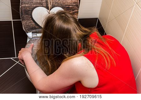 Young woman vomiting in the bathroom - morning sickness during pregnancy