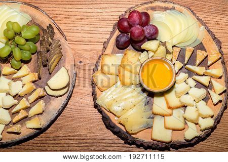 Closeup of various sorts of cheese sliced in plate on table