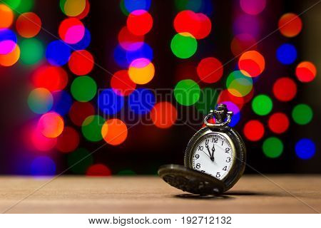Closeup vintage old clock in the bokeh on brown wood background. The clock is near midnight. Concept Christmas and happy new year or everything related to time.