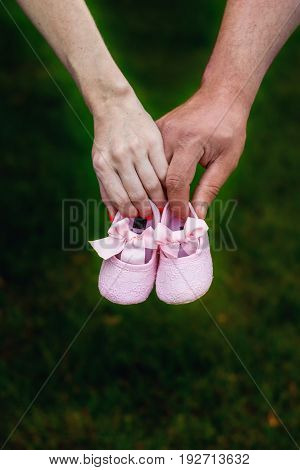 First baby girl shoes in a parent hands