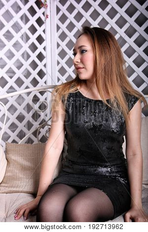 Attractive asian girl sitting on the chair and looking away.