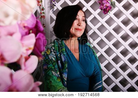 Mature asian woman sitting on couch in flower garden in luxurious dress.