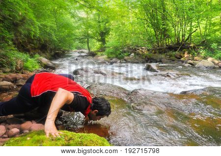Man drinking water from the river in mountains. Clean unpolluted water in the river in the wild,