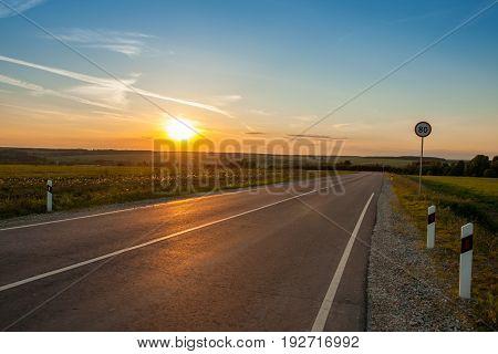 Beautiful Agricultural Landscape. Asphalt Route Road Under Sunrise Or Sunset Over Farm Fields For Agricultural Spring.