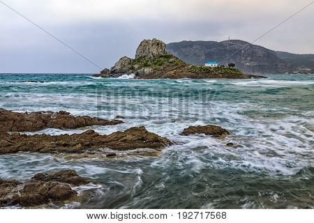 Dramatic scene of rocks washes of stormy sea with small island Kastri in Kos Greece.
