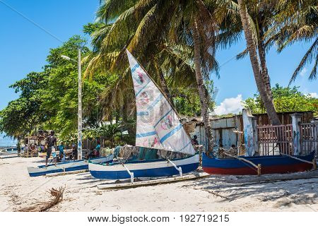 Ramena Madagascar - December 20 2015: Local villagers and traditional malagasy wooden sail boat piroga in Ramena Madagascar. Ramena is a charming steadily growing fishing village located in Diego Suarez Bay.