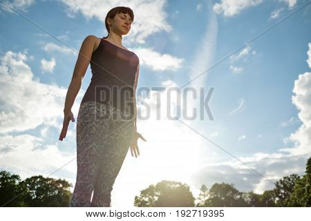 Yoga outdoor. Woman doing yoga exercises on the red mat, meditate in the park on the grass. Mountain yoga pose tadasana.
