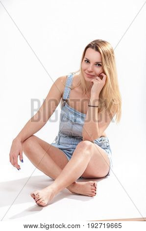 Young girl sitting on a light background