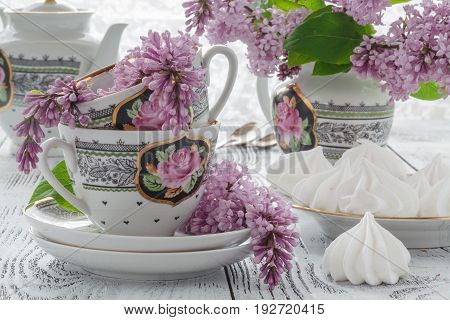 Cup Of Tea With Lilac Flowers On White Background. Summer Tea Time Concept.