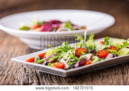 Vegetable salad. Plate of salad with vegetables on rustic oak table. Assortment of ingredients of vegetable salad.