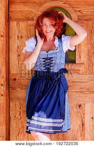 Red-haired woman in a dirndl in front of a door